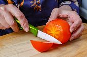 Elderly Woman Cuts Ripe Orange Persimmon By Ceramic Knife On The Wooden Cutting Board. Cutted Persim poster