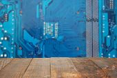 Empty Dark Rustic Wood Table With Blurred Abstract Blue Background Electronic Printed Circuit Board  poster