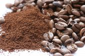 Whole and ground coffee beans scattered on white background