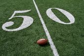 stock photo of ncaa  - American football near the fifty yardline on a green grass field - JPG