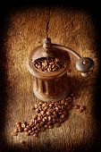 picture of wooden box from coffee mill  - Antique coffee grinder with shiny seeds on a wooden background - JPG