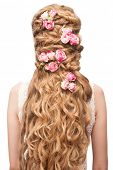 Blond Hair. Beautiful Caucasian Woman with Curly Long Hair. Bridal hairstyle decorated by flowers
