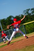 stock photo of little-league  - Little league pitcher in red jersey pitching ball - JPG