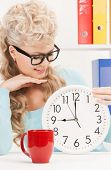 picture of attractive businesswoman with clock and red cup