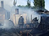 stock photo of firemen  - Smoldering remains of a ghetto house with a fireman spraying water firefighters extinguish a fire in an apartment house - JPG
