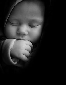 image of sleeping baby  - Sleeping Baby with thumb in the mouth on black - JPG