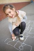 stock photo of hopscotch  - A smiling girl with a pigtail ends draw hopscotch on the pavement - JPG