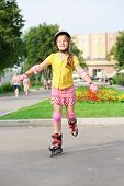 Girl in a helmet, elbow pads and knee pads roller-skating in the park