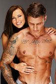 stock photo of hot pants  - Young woman embracing man with naked muscular torso - JPG