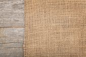 stock photo of wood  - Burlap texture on wooden table background - JPG