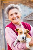 foto of little puppy  - Laughing elderly woman with her kind little puppy outdoors - JPG