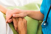 stock photo of hospital patient  - Social care provider holding senior hands in caring attitude - helping elderly people.