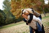 Attractive loving couple having fun in autumn park, laughing, piggyback.