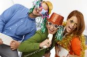 Joyful new year's eve office band, workers using phone and keyboard as instrument, singing, having f