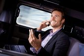 stock photo of limousine  - Handsome young businessman traveling in limousine - JPG
