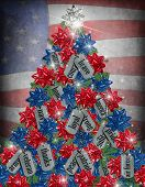 stock photo of tribute  - Dog tags with gift bows on a Christmas tree with flag background - JPG