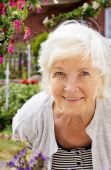 image of elderly woman  - Senior woman portrait outdoor in front of the garden smiling to camera - JPG