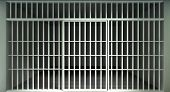 picture of lockups  - A front view of a full brick jail cell with white iron bars and a closed sliding bar door on a dark background - JPG