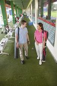 stock photo of caddy  - Young happy couple leaving  golf course with golf clubs and caddy - JPG