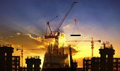 stock photo of engineering construction  - big crane and building construction against beautiful dusky sky use for construction industry and engineering - JPG