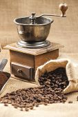 still life of coffee beans in jute bag with coffee grinder