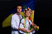 foto of national costume  - Proud couple in the Ukrainian national costumes with Ukrainian flag - JPG
