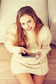 Beautiful caucasian woman sitting on the wooden floor with tablet.
