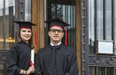 foto of youg  - Portrait of a youg couple in the graduation day posing in front of the gate of the University - JPG