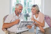 Mature couple reading newspaper while drinking coffee at home