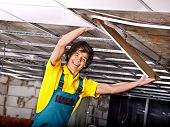 foto of suspenders  - Man in builder uniform installing suspended ceiling - JPG