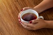 woman holding hot cup of tea on wooden table