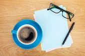 Blank lined paper with coffee, office supplies and glasses on wooden table. Above view