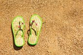 Pair Of Flip-flops In The Wet Sand At Seaside
