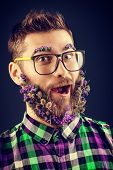 Expressive young man in glasses and a beard of flowers.