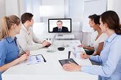 foto of training room  - Businesspeople Sitting In Conference Room Looking At Monitor - JPG