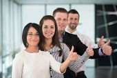Team of smiling business people with thumbs up standing in modern office