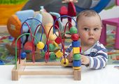 foto of playgroup  - Toddler or a baby child playing with puzzle on a low table in a colorful children room in a nursery or preschool - JPG