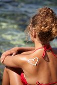 stock photo of sunburn  - teenage girls back with sunburn and heart of sun lotion - JPG