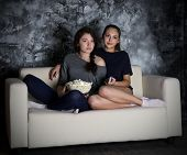 Two young girls looks TV