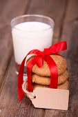 Glass of milk and a stack of homemade cookies, tied with a red ribbon and a gift tag, with space for
