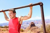 foto of pulling  - Exercising Fitness athlete man training pull ups in amazing nature landscape of Grand Canyon - JPG