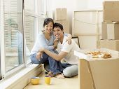picture of life event  - Asian couple surrounded by moving boxes - JPG