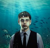 foto of gullible  - Underwater scene of a businessman with fishes - JPG