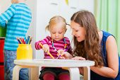 stock photo of daycare  - Young mother and her daughter drawing together - JPG