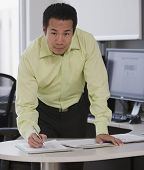 picture of interrupter  - Asian businessman writing at desk - JPG