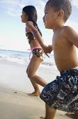 pic of pacific islander ethnicity  - Pacific Islander siblings running on beach - JPG