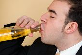 image of chug  - A young business man enjoying a nice cold bottle of beer after work - JPG