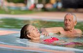 pic of hot couple  - Senior couple enjoying sun and holiday in the pool with hot water - JPG