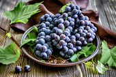 pic of merlot  - Fresh grape on a plate on a wooden table - JPG