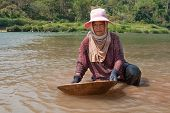 stock photo of ou  - woman washing gold in river portrait of asian at nam ou in Laos - JPG
